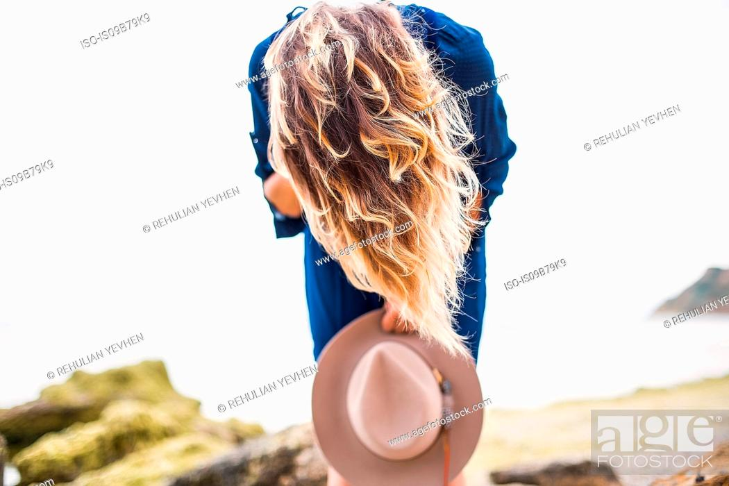 Stock Photo: Mid adult woman in coastal setting, holding hat, bending over, hair covering face.