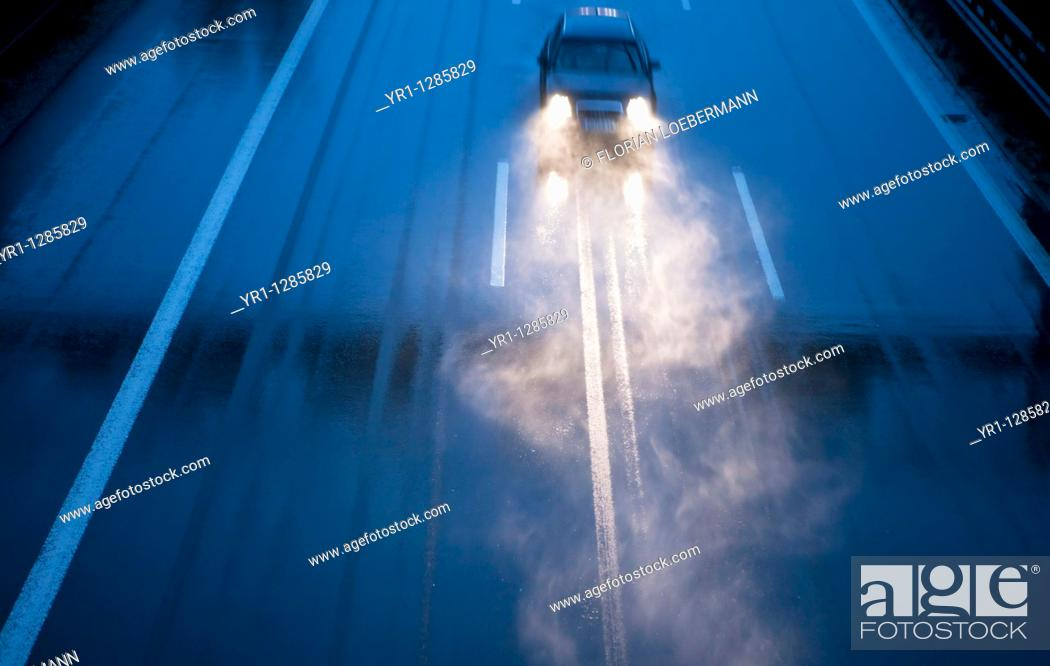 Stock Photo: A lonely car on the german Autobahn during heavy rain at dusk.