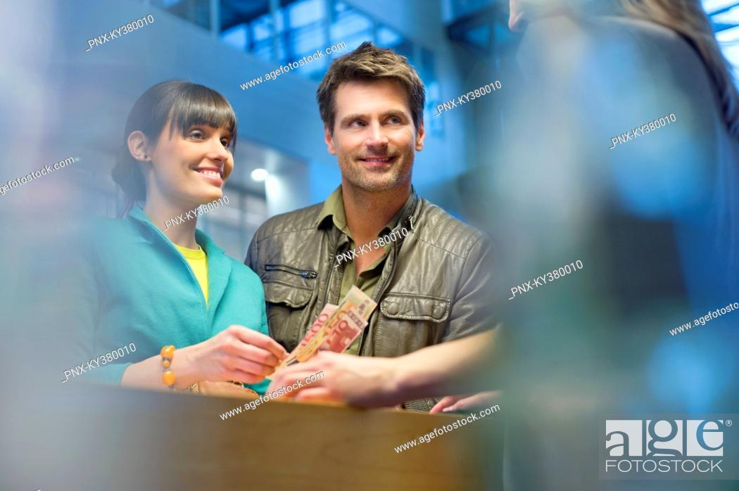 Stock Photo: Happy couple standing at a bank counter.