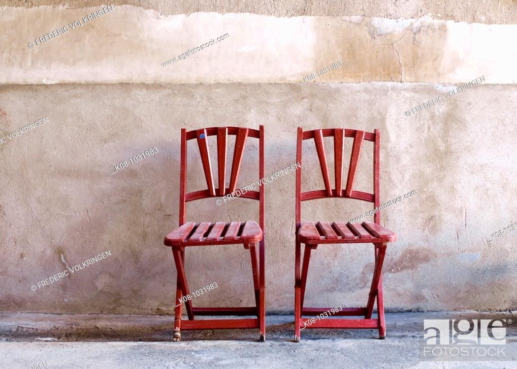 Stock Photo: Two red folding chairs against wall.