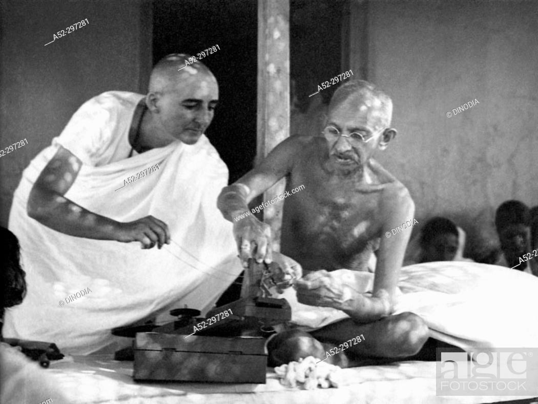 Gandhi repairing his charkha (spinning wheel) assisted by