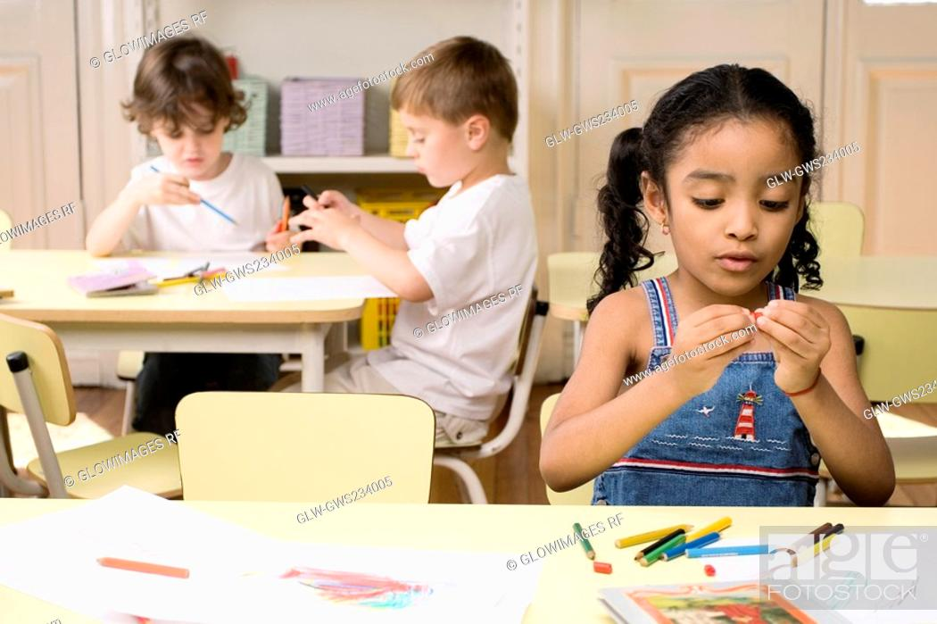 Stock Photo: Two boys and a girl drawing in a classroom.
