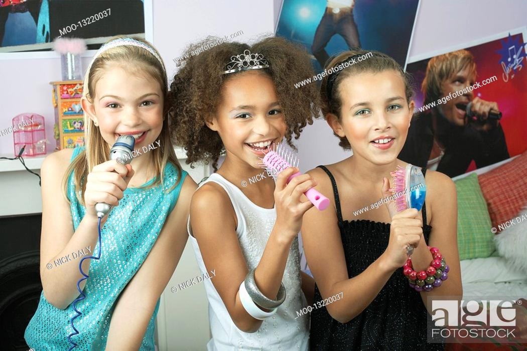 Stock Photo: Girls using brushes microphones to sing at a Slumber Party.