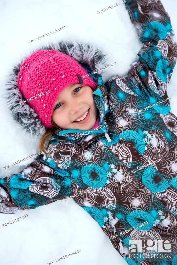 Photo de stock: Smiling girl lying on snow.
