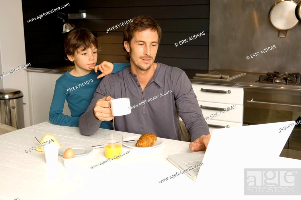 Stock Photo: Mid adult man working on a laptop with his son standing behind him.