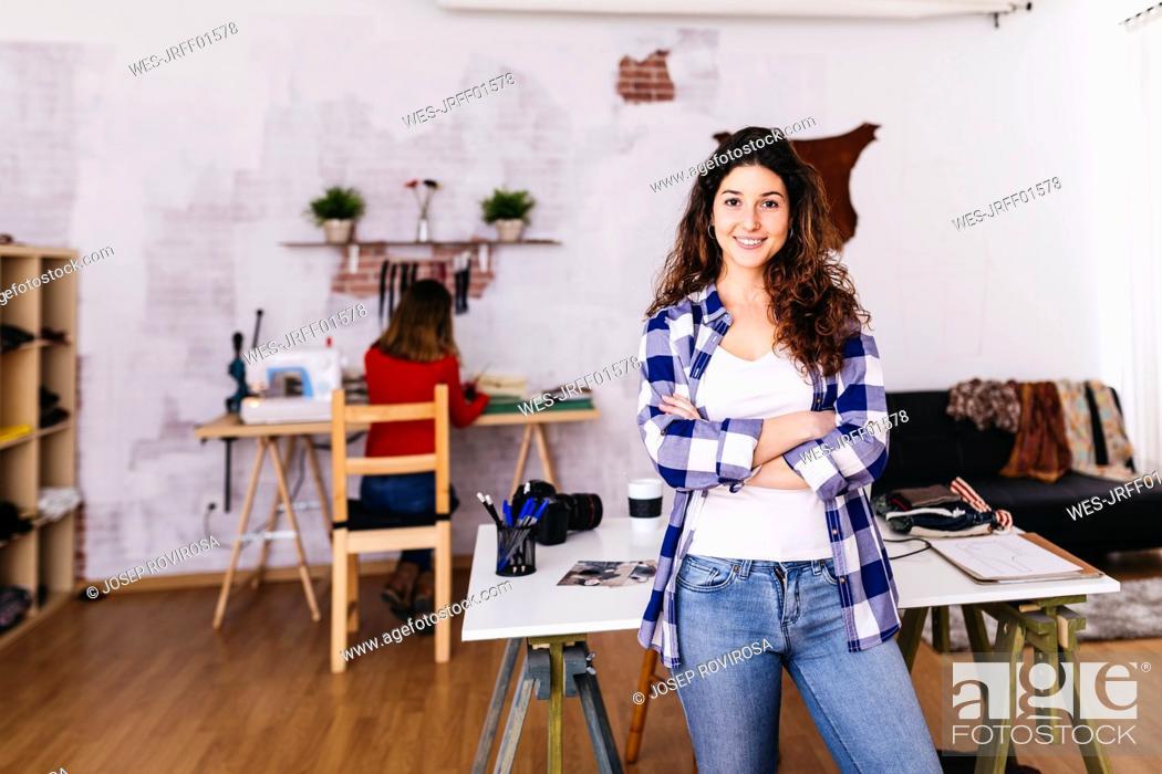 Stock Photo: Portrait of smiling fashion designer in studio.