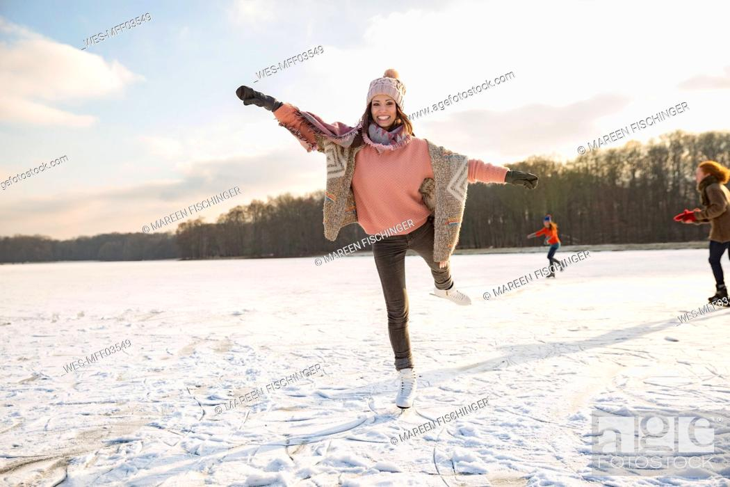 Stock Photo: Woman dancing with ice skates on frozen lake with friends.