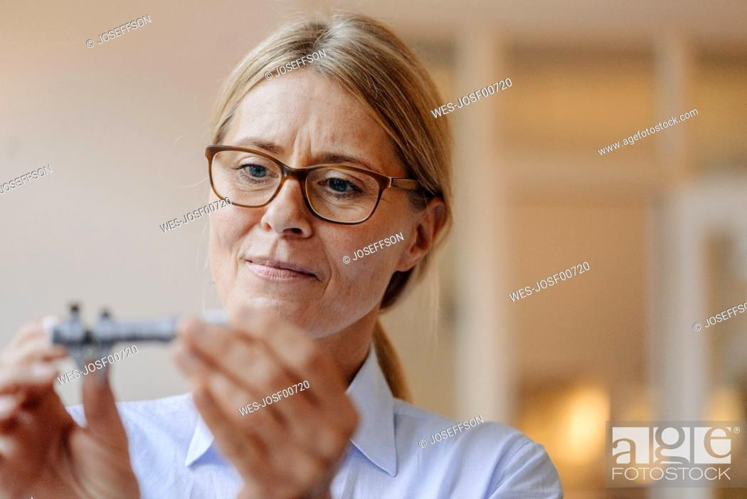 Stock Photo: Portrait of businesswoman holding and looking at something.