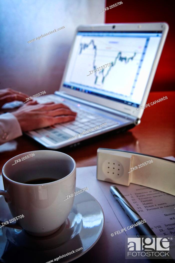 Stock Photo: Close-up of female hands making notes in the laptop at office hile taking a cup of coffee.