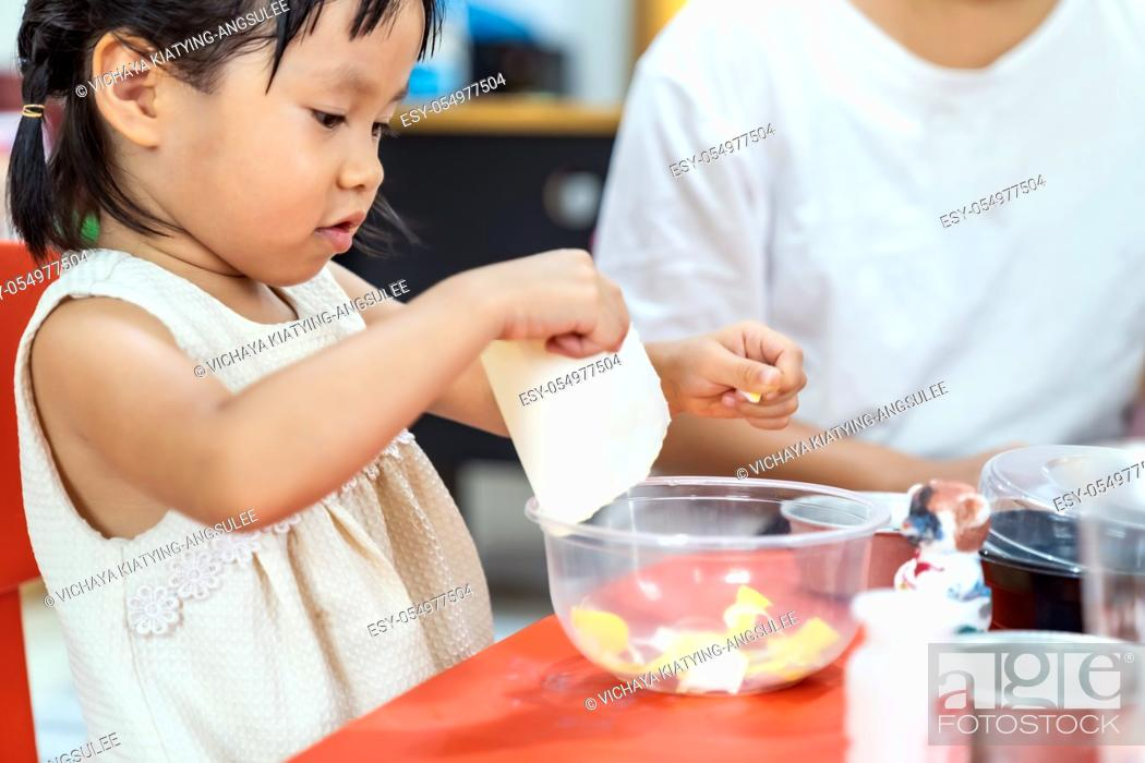 Stock Photo: Asian girl kid playing toy and colorful paper for art lesson at living room in home as home schooling while city lockdown because of covid-19 pandemic across.