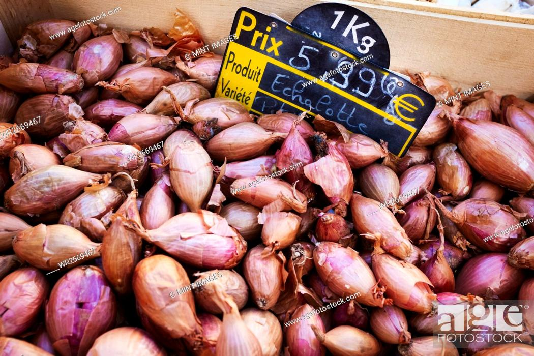 Stock Photo: A market stall display of shallots, fresh vegetables, onions for sale.