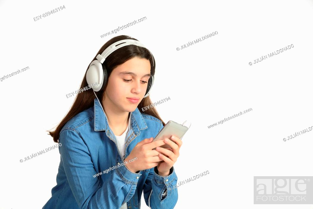 Stock Photo: Young teenager with his headphones, listening to music through the mobile.