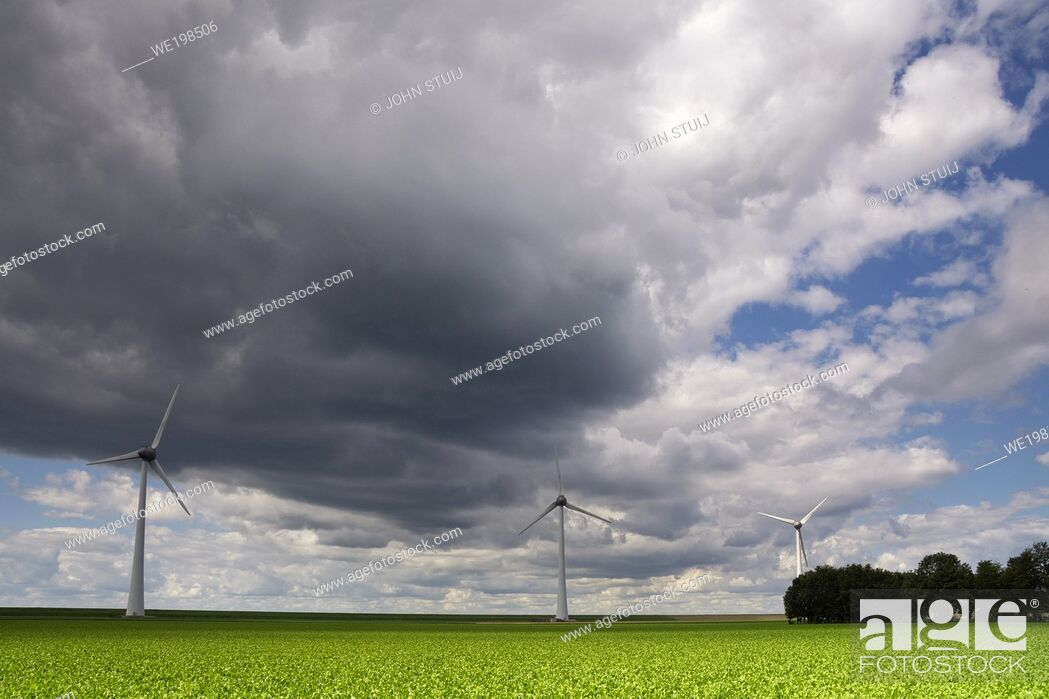 Stock Photo: Windmills in a field under heavy clouds close to the Dutch village Urk.