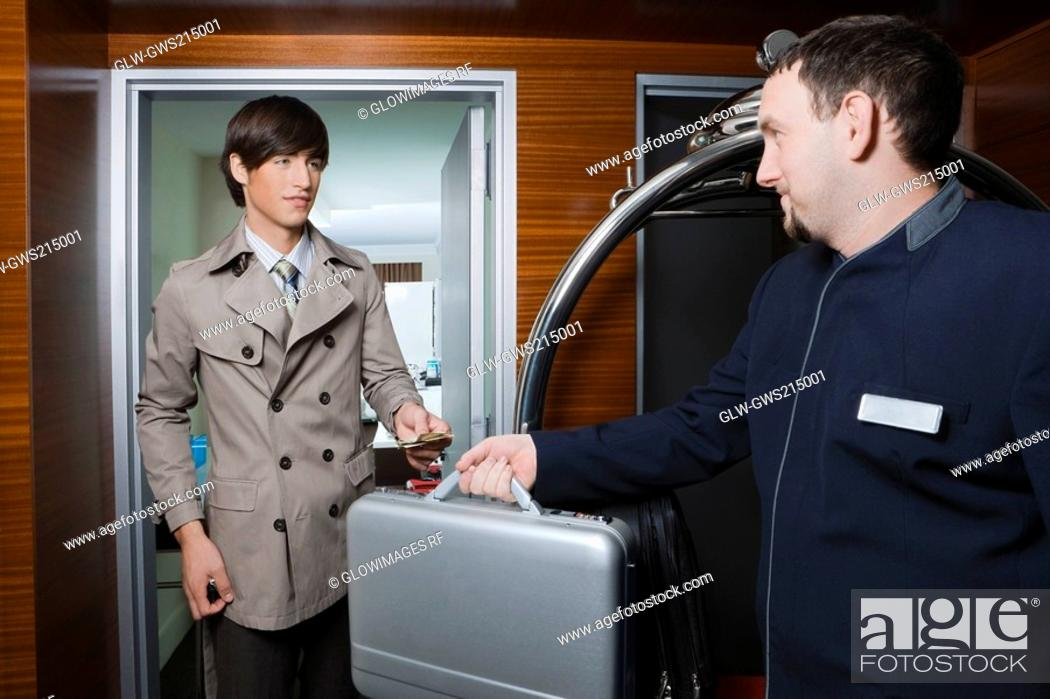 Stock Photo: Room service man handing over a briefcase to a businessman.