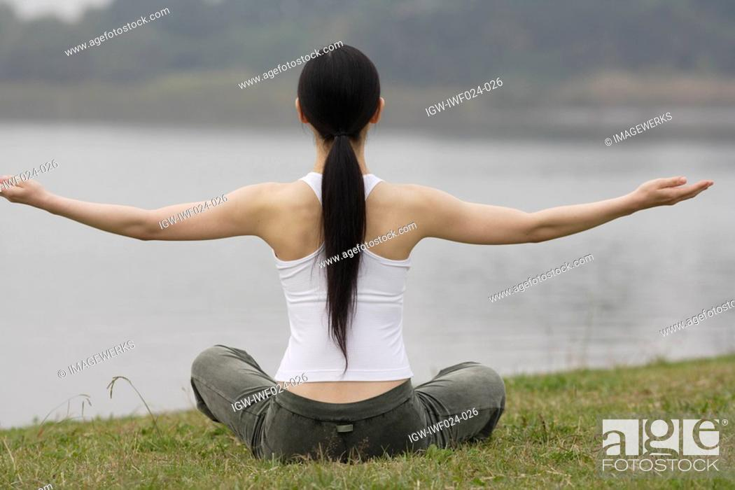 Stock Photo: Rear view of a young woman in lotus position.