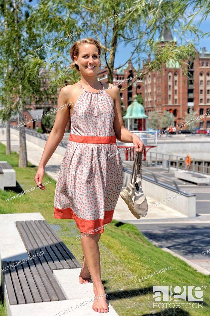 Stock Photo: Woman walking barefoot on a wall.