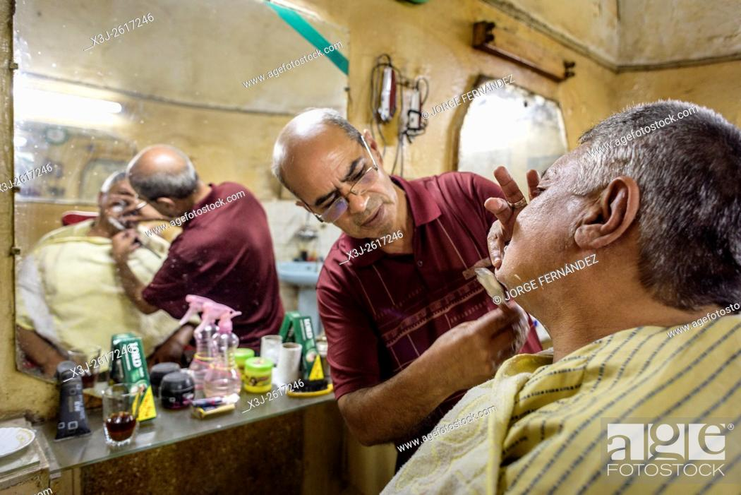 Stock Photo: Barber shaving a client with a razor blade in front of a mirror.