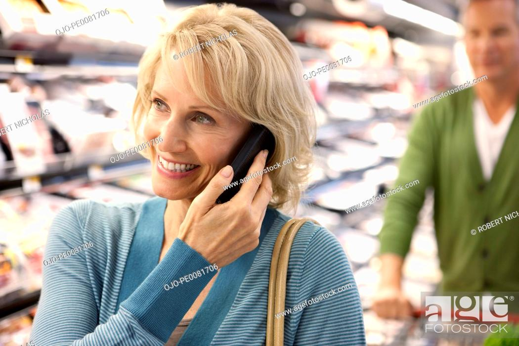 Stock Photo: Older woman on cell phone in supermarket.