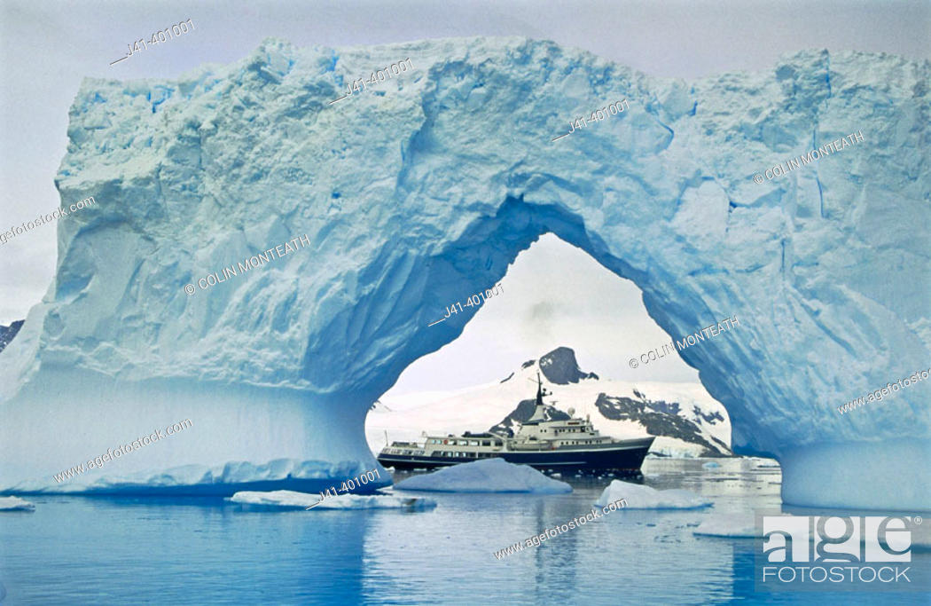 Stock Photo: Motor yatch 'Itasca' framed in iceberg arch, Petermann Island, Antarctic peninsula.