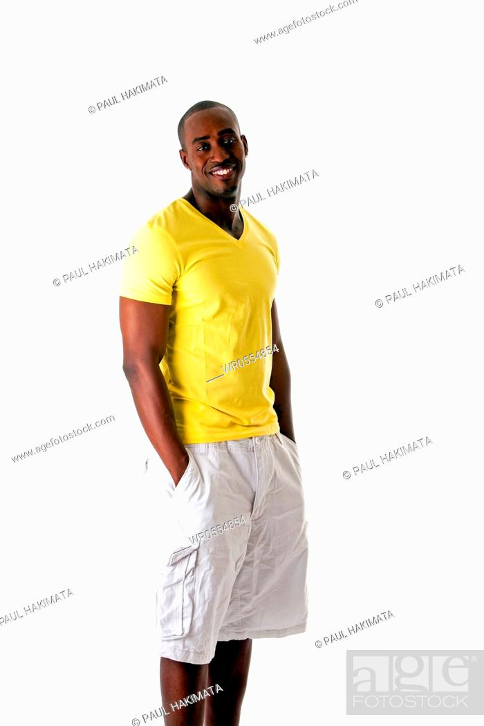 Imagen: Handsome sporty African American man in yellow shirt and white shorts standing with hands in pocket and big smile, isolated.