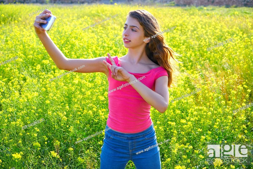 Photo de stock: Teen girl serfie video photo in spring meadow gesturing.