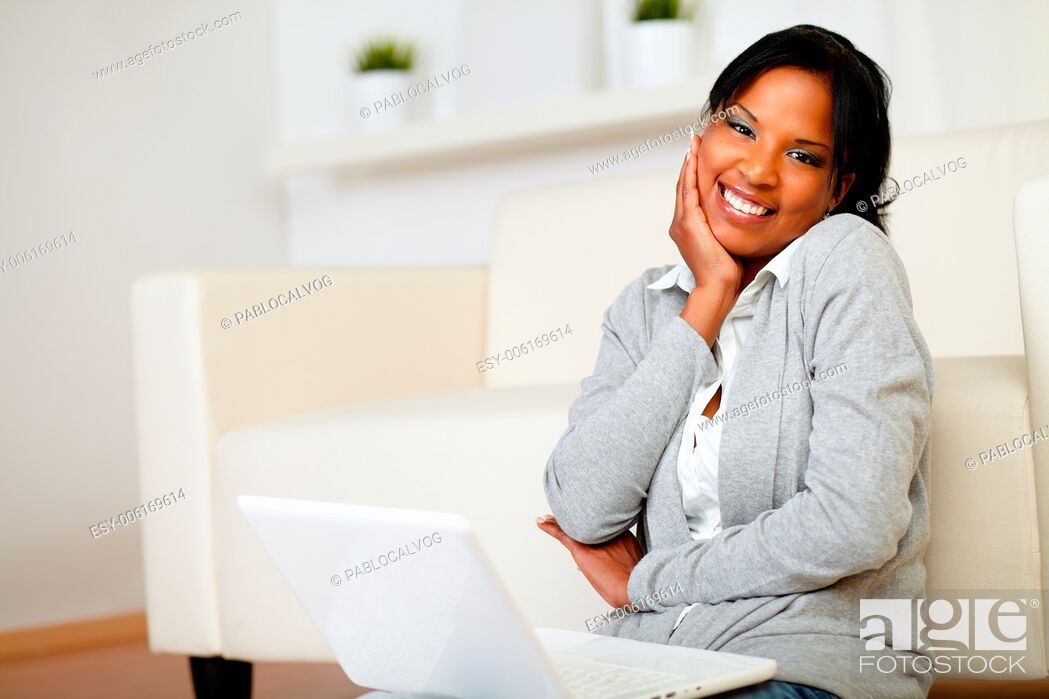 Stock Photo: Portrait of a cute black woman smiling at you while is sitting on the floor with laptop.