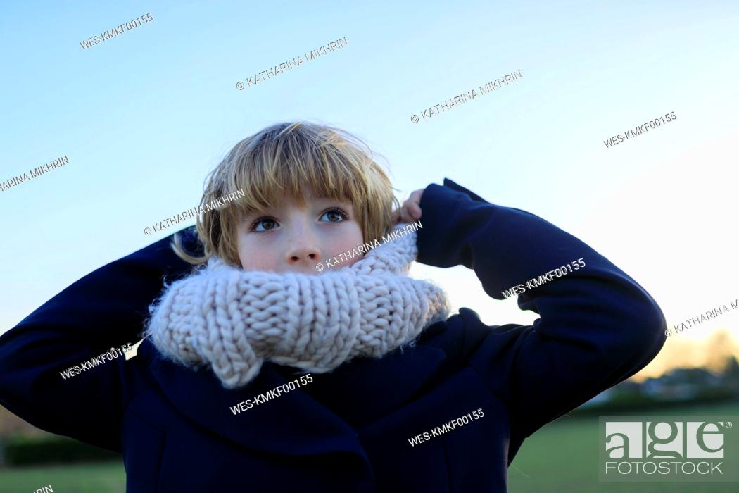 Photo de stock: Boy with knitted round scarf at sunset.