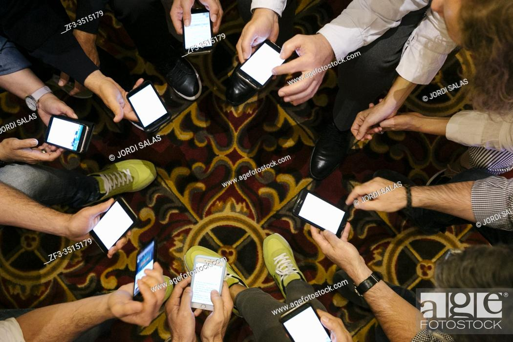 Stock Photo: Hands of people with their smartphones working during a meeting.