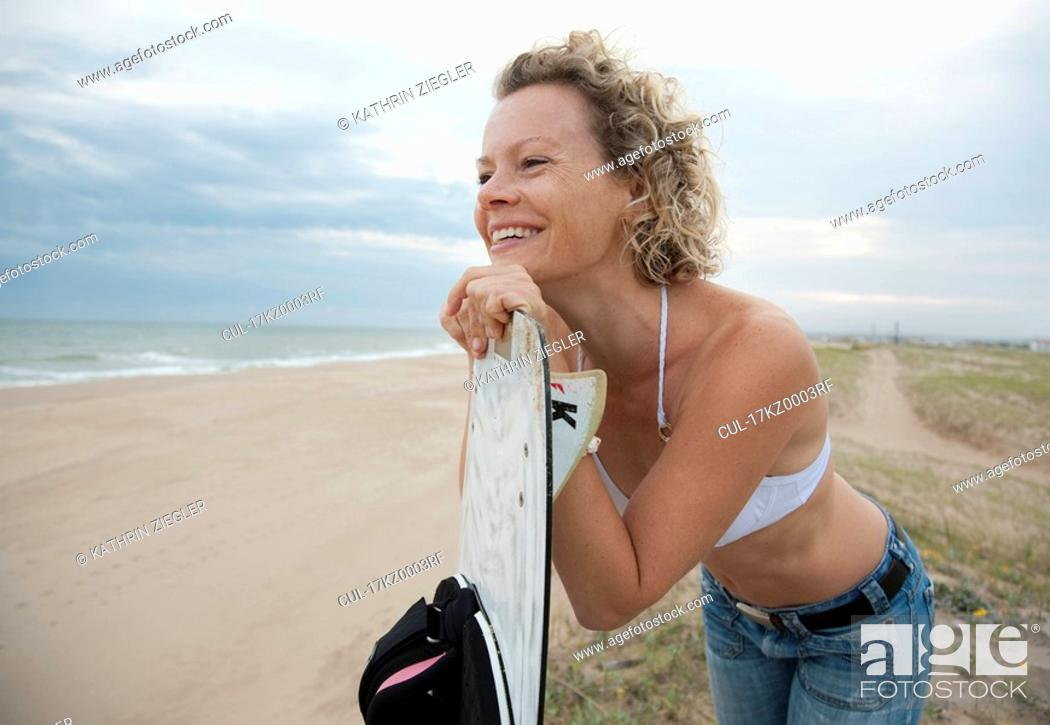 Stock Photo: woman with kite board, overlooking beach.
