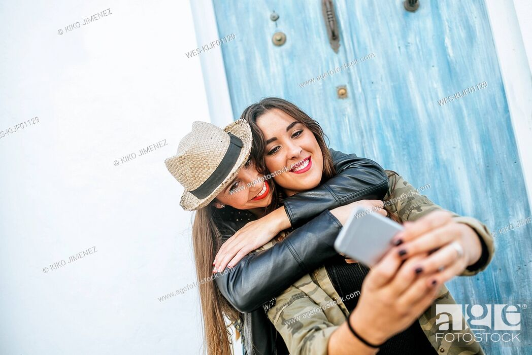 Stock Photo: Two happy young women taking a selfie with a smart phone.