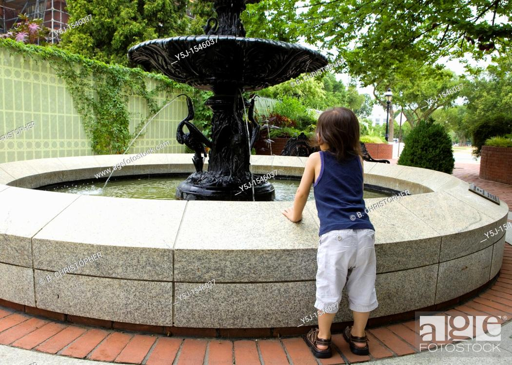 Stock Photo: Small child leans on a water fountain to get a better look.
