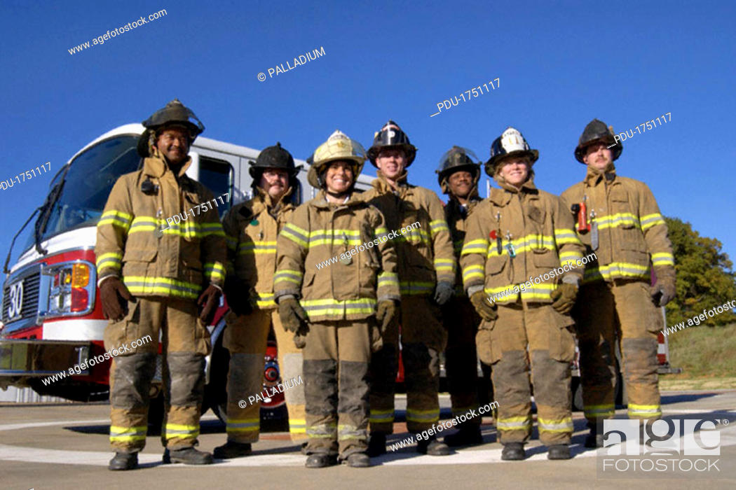 Stock Photo: A group of seven firemen and women standing outside in their gear, in front of a fire truck.