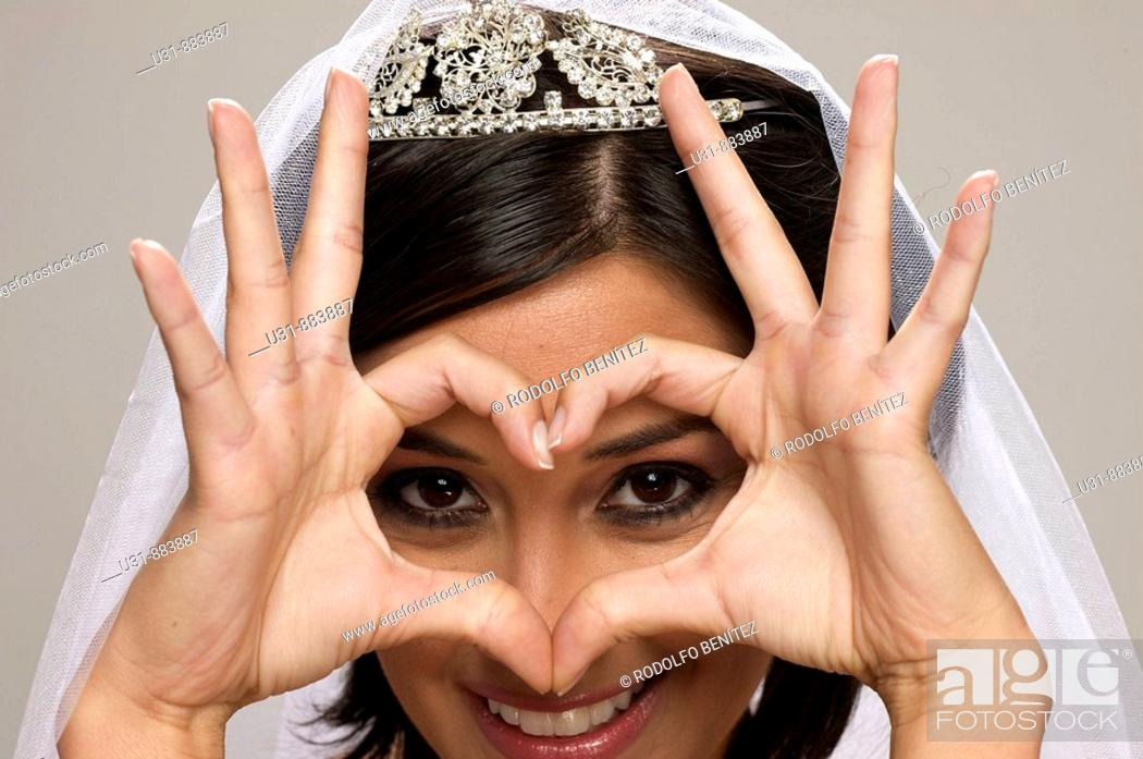 Stock Photo: Bride in her 20s draws a heart with her hands at the camera.
