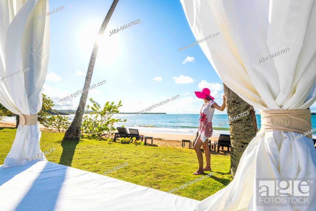 Stock Photo: Playa Moron, Las Terrenas, Samana Peninsula, Dominican Republic. Beautiful woman admiring the view from by a beach bed (MR).