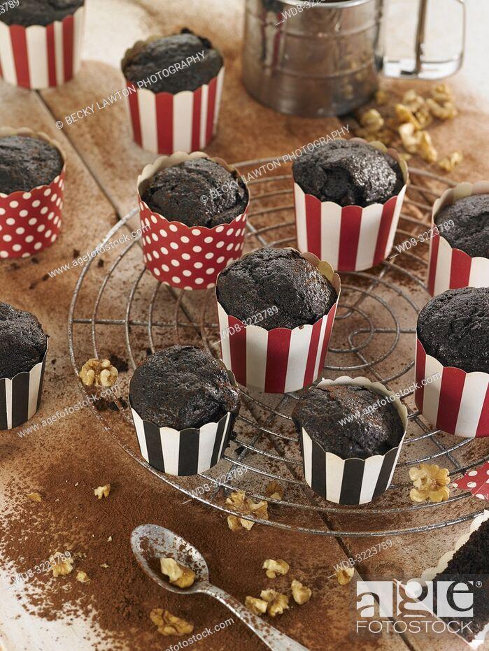 Photo de stock: muffins de chocolate con nueces en tarrinas / chocolate muffins with walnuts.
