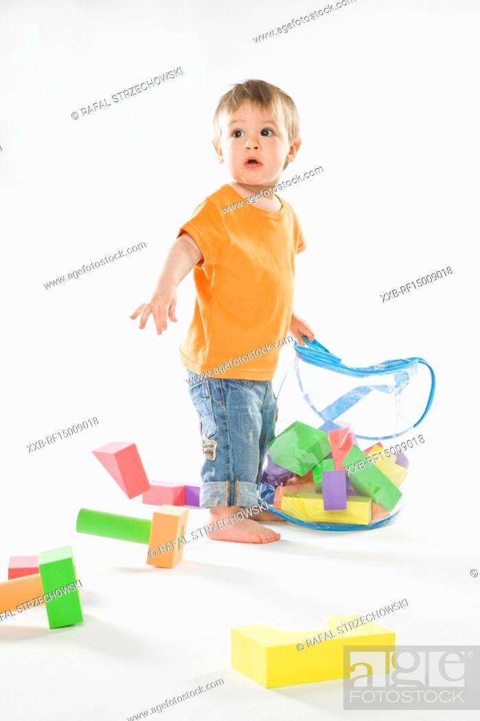 Stock Photo: baby tidy up bricks into bag.
