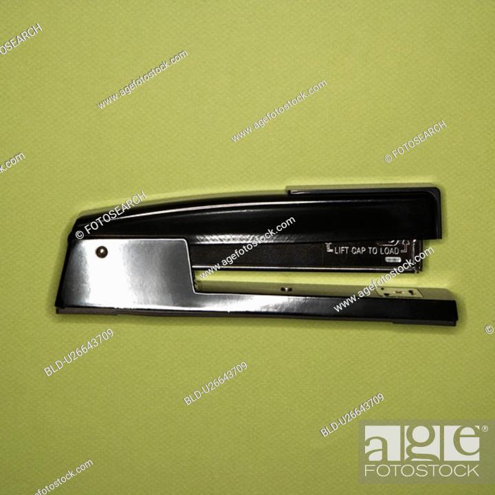 Stock Photo: Black stapler on green background.