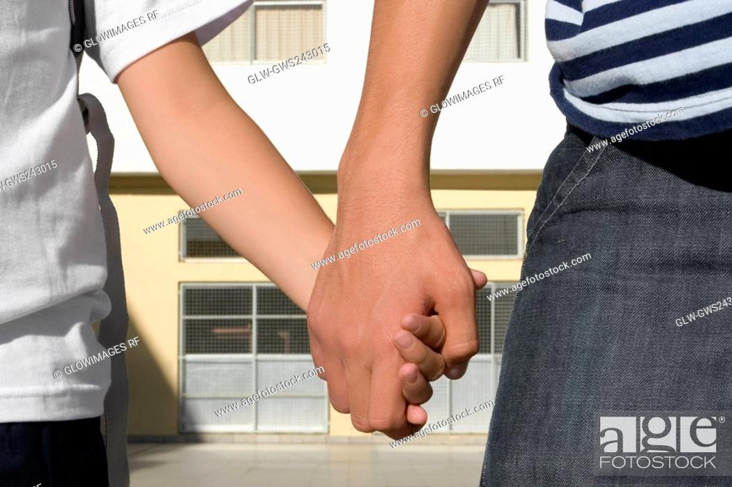 Stock Photo: Mid section view of a boy holding hands of his sister.
