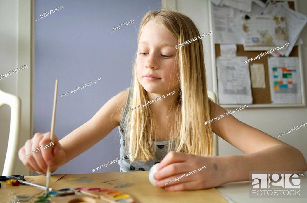 Stock Photo: Young girl painting easter eggs.