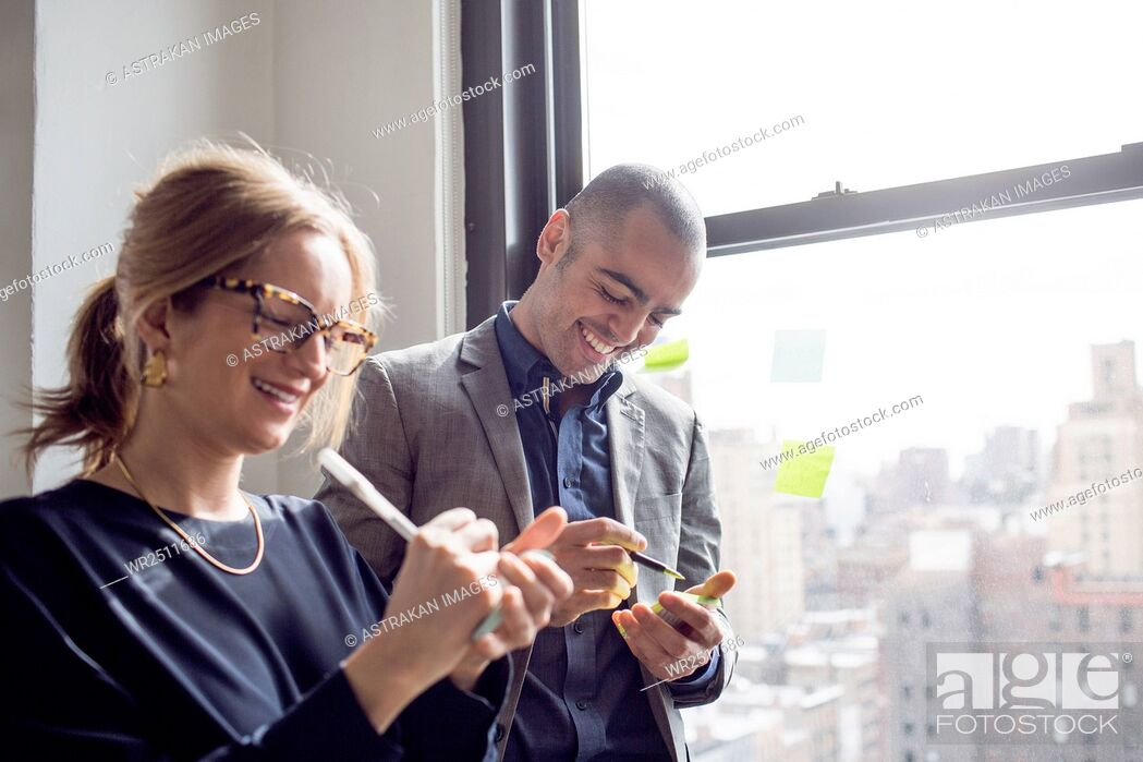 Stock Photo: Businessman and businesswoman writing on sticky notes by window.