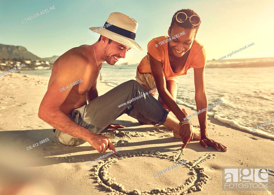 Stock Photo: Young couple drawing in sand on sunny summer ocean beach.
