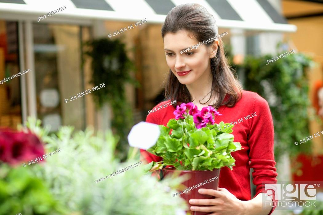 Stock Photo: Woman holding a potted plant in a flower shop.
