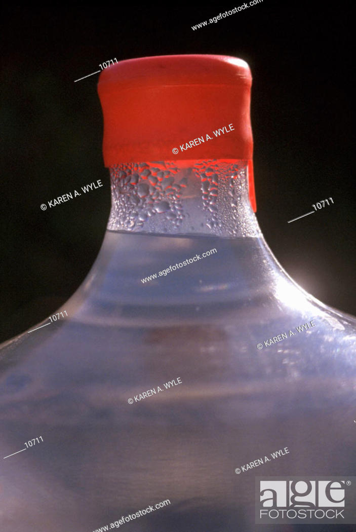 Stock Photo: Water bottle with red top, small drops of condensation.