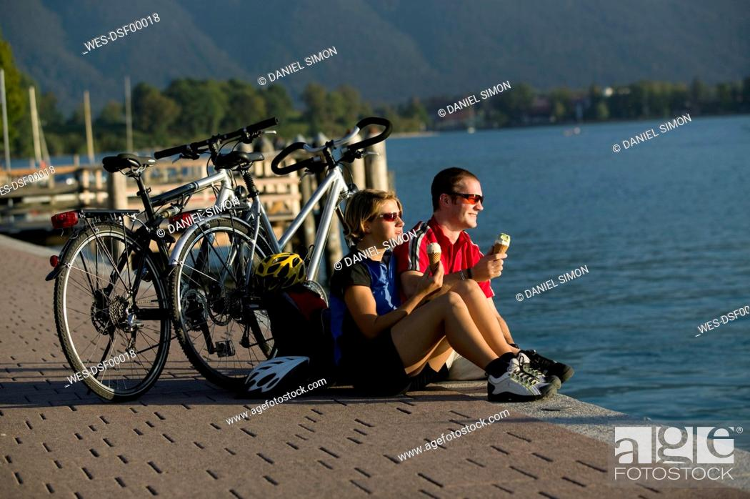 Stock Photo: Germany, Bavaria, Tegernsee, Couple with mountain bikes eating ice cream.