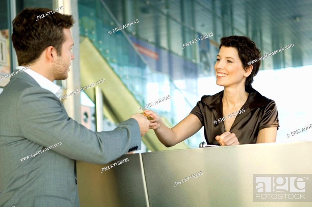 Stock Photo: Businessman giving a credit card to a hotel receptionist.