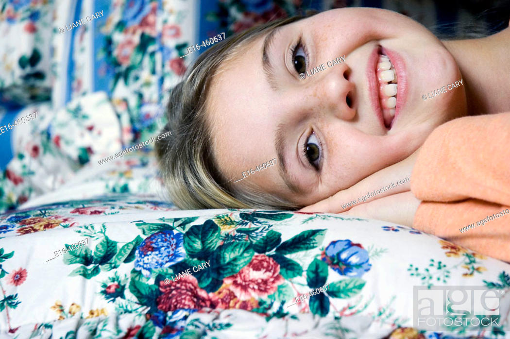 Stock Photo: smiling girl on bed.