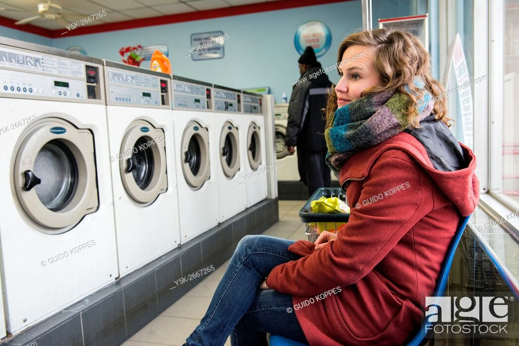 Stock Photo: New York City, USA. Young brunette woman waiting for her laundru to finish inside a Chinese run laundrette.