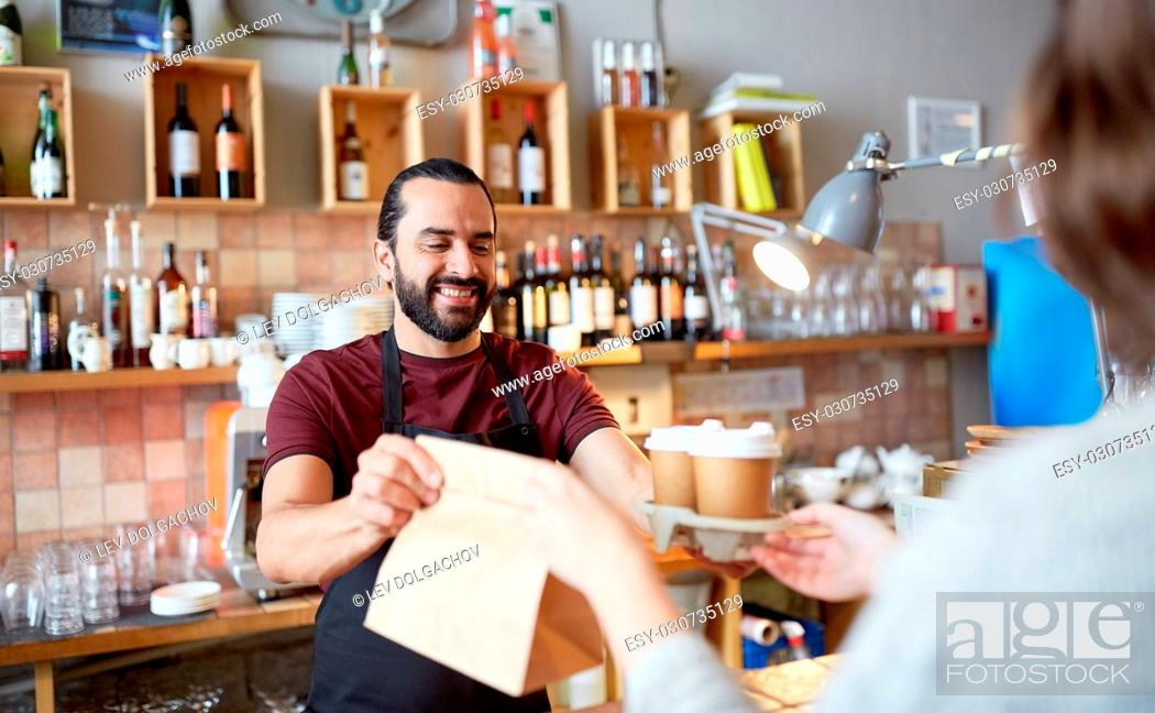 Stock Photo: small business, people, takeaway and service concept - happy man or waiter giving bag and paper cups with hot drinks to customer at coffee shop.