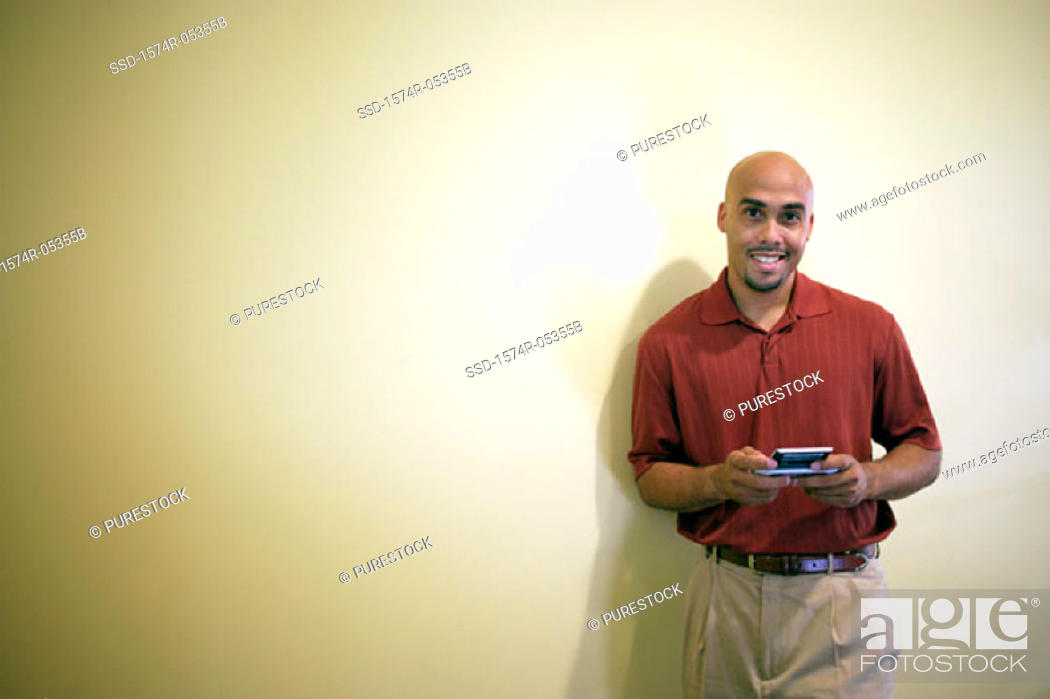 Stock Photo: Portrait of a businessman standing in an office holding a palmtop.