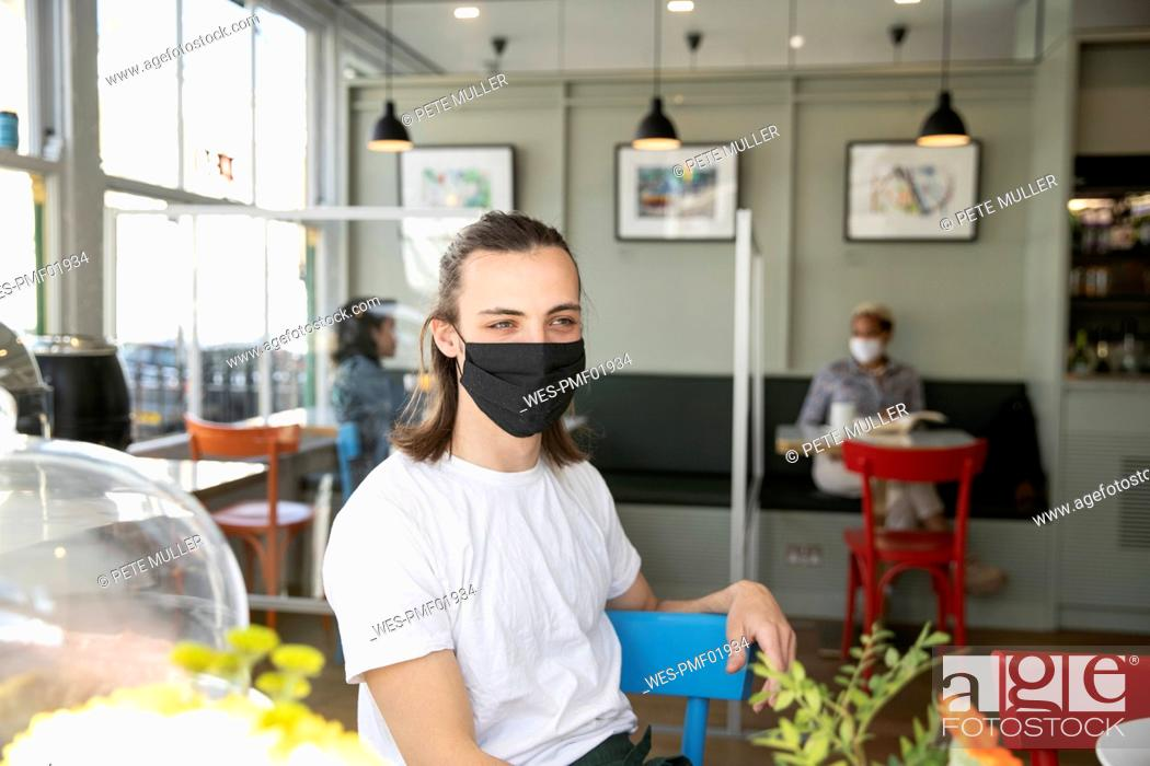 Stock Photo: Male cafe owner in protective face mask looking away while sitting in cafe during pandemic.